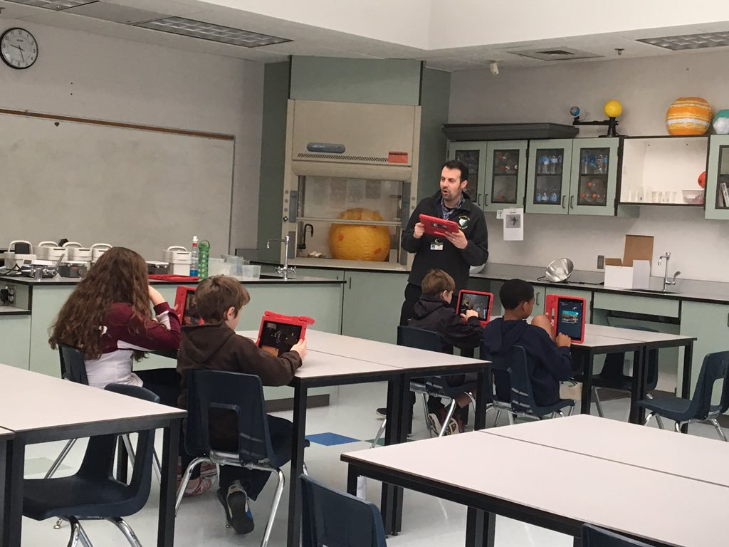 Tom Mullaney using an iPad to lead four students on a Google Expedition.